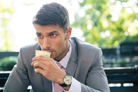 hombre tomando cafe: Retrato de un hombre de negocios confidente que se sienta en el banquillo y el consumo de café al aire libre Foto de archivo