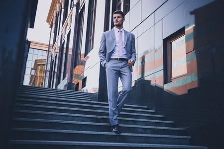 Ritratto integrale di un uomo d'affari premuroso che cammina sulle scale all'aperto