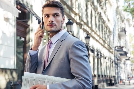 bel homme: Portrait d'un bel homme d'affaires à parler au téléphone à l'extérieur et regarder ailleurs