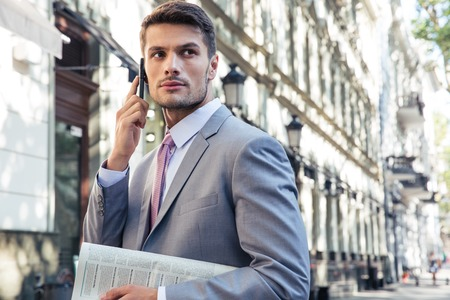 Portrait of a handsome businessman talking on the phone outdoors and looking away
