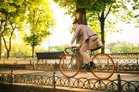 Zakenman rijden fiets naar het werk in park