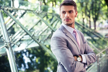 fold: Portrait of a confident businessman standing with arms folded outdoors near glass building Stock Photo