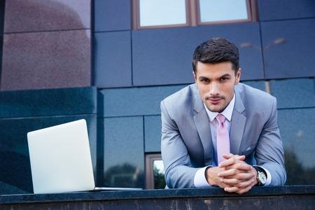 自信を持っている実業家で、屋外のラップトップ コンピューターの肖像画。カメラを目線