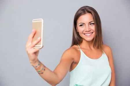 Glimlachend jong meisje dat selfie foto op smartphone over grijze achtergrond