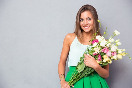 Portrait of a cute happy woman holding flowers over gray background. Looking at camera Stock Photo