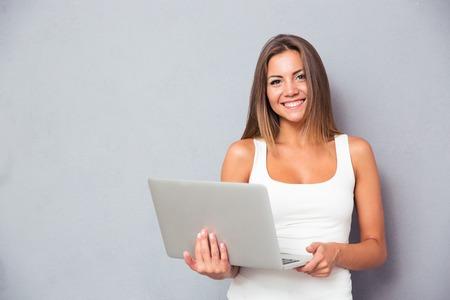 joven de pie con la computadora portátil sobre fondo gris sonriendo