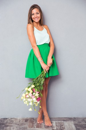 Full length portrait of a happy pretty girl holding bouquet with flowers on gray background