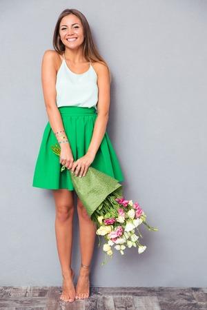 행복 한 여자의 전체 길이 초상화는 회색 배경에 꽃 꽃다발을 들고