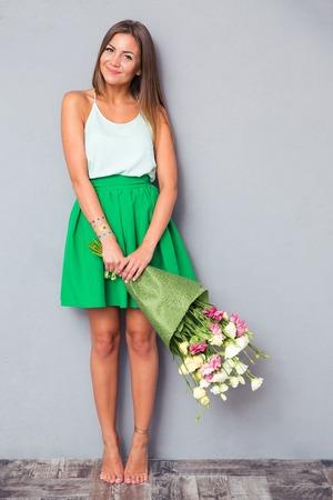 In voller Länge Porträt einer lächelnden niedliche Mädchen mit Blumen Bouquet auf grauem Hintergrund Standard-Bild - 42975322