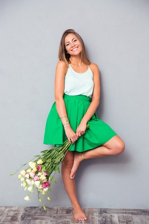 Full length portrait of a smiling cute woman standing with flowers on gray background. Looking at camera