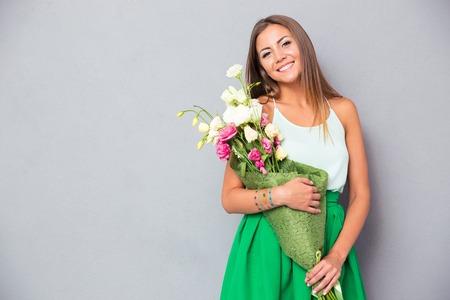 회색 배경 위에 꽃을 들고 행복 예쁜 여자입니다. 카메라를 보면서 스톡 콘텐츠 - 42975329