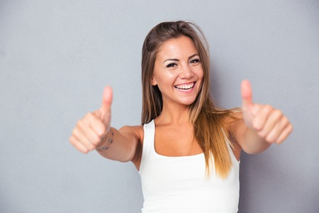 Vrolijke mooie meisje blijkt thumbs up over grijze achtergrond. Kijken naar de camera