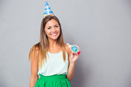 noisemaker: Happy young girl in birthday hat and whistle standing over gray background and looking at camera