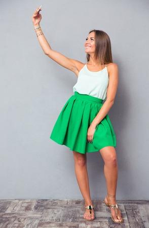 灰色の背景にスマート フォンで selfie 写真を作る幸せな女の子の完全な長さの肖像画 写真素材