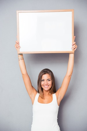 woman holding sign: Smiling young girl holding blank board over gray background. Looking at camera Stock Photo