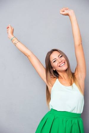 woman hands up: Portrait of a smiling woman with raised hands up over gray background. Looking at camera