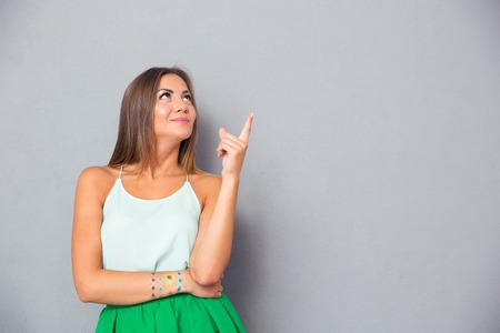 Happy cute woman pointing finger up at copyspace over gray background