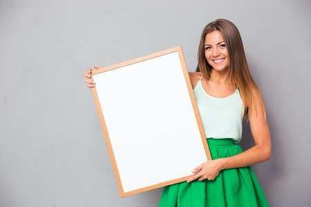 isolated sign: Happy girl holding blank board over gray background and looking at camera Stock Photo