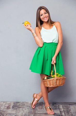 Full length portrait of a smiling attractive woman holding basket with vegetables over gray background Imagens