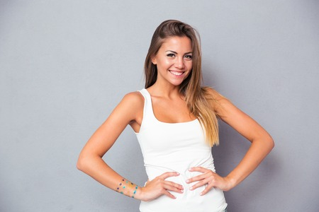 Happy attractive girl standing over gray background and looking at camera Foto de archivo