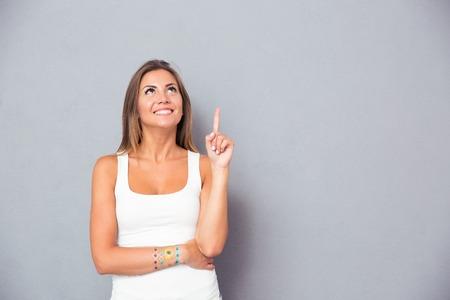 Glimlachend jonge vrouw wijzende vinger up over grijze achtergrond