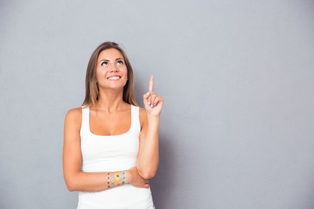 advertising woman: Smiling young woman pointing finger up over gray background