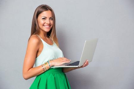 かわいい女の子灰色の背景の上のラップトップを使用して、アメーラを見て笑みを浮かべてください。