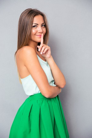 finger on lips: Portrait of a beautiful woman showing finger over lips on gray background. Looking at camera Stock Photo