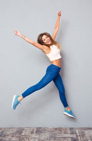 Cheerful pretty girl jumping over gray background. Looking at camera
