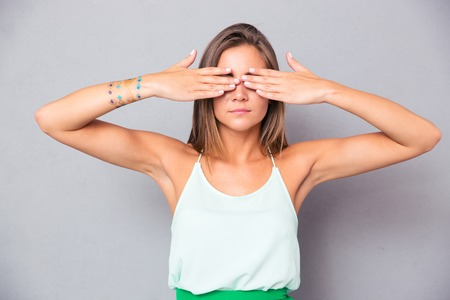 gray eyes: Young girl covering her eyes with hands over gray background
