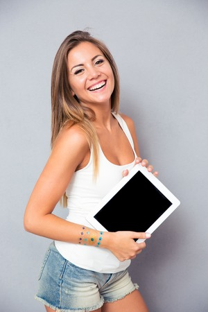 Portrait of a young smiling woman holding tablet computer over gray background