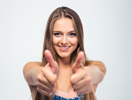 白い背景で隔離まで若い女の子を示す親指を笑ってください。