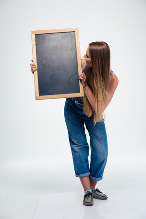 it is isolated: Full length portrait of a female student holding blank board and looking on it isolated on a white background