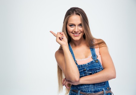 direction sign: Portrait of a smiling young woman pointing finger away isolated on a white background. Looking at camera Stock Photo