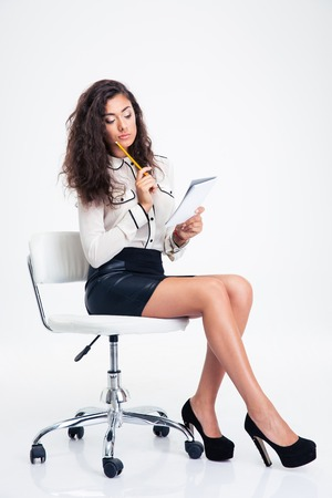 pencil skirt: Pensive businesswoman sitting on the office chair and holding notebook with pencil isolated on a white background