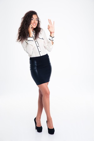 succesful: Full length portrait of a businesswoman talking on the phone and showing ok sign with fingers isolated on a white background