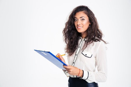 Happy young businesswoman holding clipboard isolated on a white background. Looking at camera