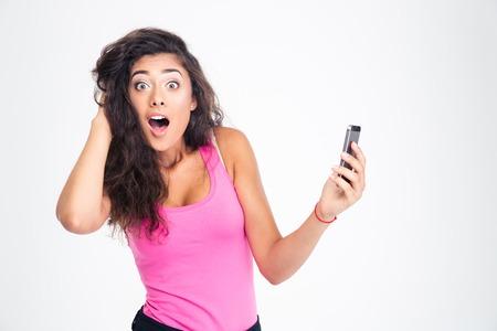 Mujer joven Shocked pie con smartphone y mirando a la cámara aislada en un fondo blanco