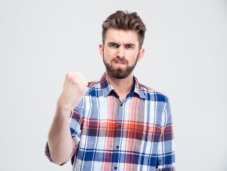 Serious man showing fist at camera isolated on a white background