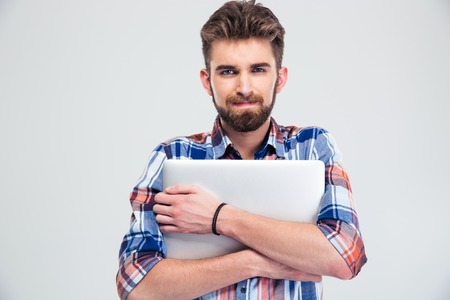 unshaved: Portrait of a unshaved handsome man holding laptop isolated on a white background