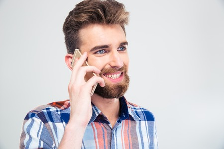 smiling man: Portrait of a young smiling man talking on the phone isolated on a white background Stock Photo
