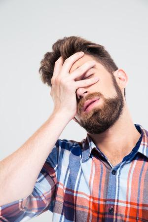 Portret van trieste man die zijn gezicht met de hand geïsoleerd op een witte achtergrond