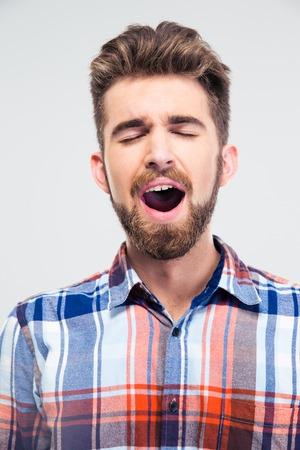 cantando: Retrato de un hombre joven que canta con los ojos cerrados aislados en un fondo blanco