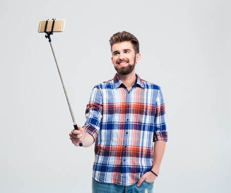 making faces: Happy casual man making selfie photo with stick isolated on a white background Stock Photo