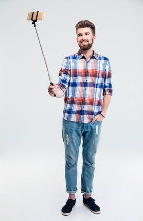 stick people: Full length portrait of a smiling man making selfie photo with stick isolated on a white background