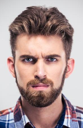 personas enojadas: Retrato del primer de un hombre serio que mira la c�mara aislada en un fondo blanco