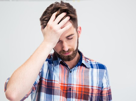 Portrait of frustrated man standing isolated on a white background