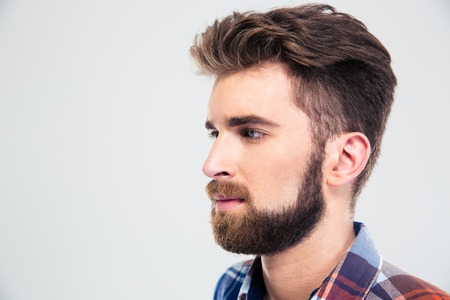 personas mirando: Primer retrato de un hombre guapo con barba que parece lejos aislado en un fondo blanco Foto de archivo