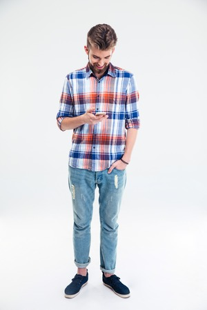 smartphone: Full length portrait of a handsome man using smartphone isolated on a white background