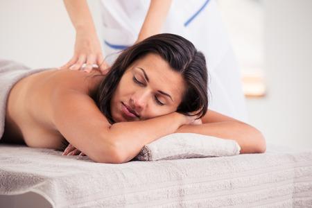 eye massage: Relaxed woman lying on massage lounger in a wellness center